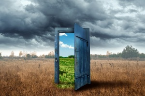 Creative background. Old wooden door, blue color, in the box. Transition to a different climate. The concept of climate change, portal, magic. Copy space.